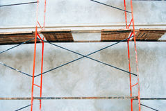 Red scaffolding. Grey wall background. Royalty Free Stock Image