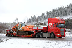 Red Scania R500 Hauls Daewoo Excavator on Winter Road Royalty Free Stock Photography
