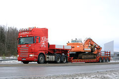 Red Scania R500 Hauls Daewoo Excavator on Winter Road Stock Image