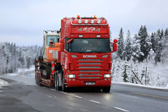 Red Scania R500 Hauls Daewoo Excavator on Winter Road Stock Photo