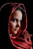 Red scarf. Low-key portrait of a young woman wearing a red scarf Stock Image