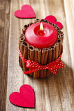 Red scented candle decorated with cinnamon sticks. Party decor Stock Image