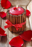 Red scented candle decorated with cinnamon sticks. Royalty Free Stock Image