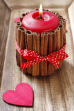 Red scented candle decorated with cinnamon sticks. Rose petals around Royalty Free Stock Photography