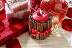 Red scented candle decorated with cinnamon sticks. Rose petals a Stock Photo