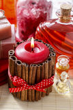 Red scented candle decorated with cinnamon sticks. Rose petals a Stock Images