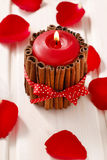 Red scented candle decorated with cinnamon sticks. Rose petals a Royalty Free Stock Image
