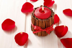 Red scented candle decorated with cinnamon sticks. Rose petals a. Round. Party decoration Royalty Free Stock Photography