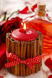 Red scented candle decorated with cinnamon sticks. Rose petals a Royalty Free Stock Photography