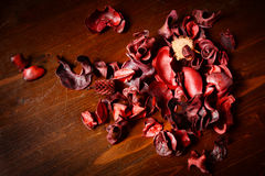 Red scented potpourri on dark wooden table. Background royalty free stock photo