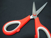 Red scissor in black background Royalty Free Stock Images