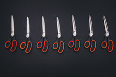 Red scissors are on the black table Stock Photos