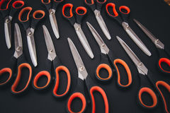 Red scissors are on the black table Stock Images