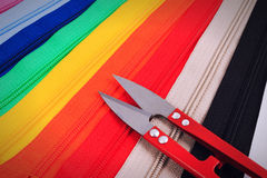 Red scissors on colorful zippers in different colors. Stock Photos