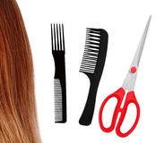Red scissors, combs and brown hair isolated on white Royalty Free Stock Photography