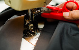 Red scissors helping a dress making process, sewing machine on blue fabric.  Stock Photo