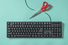 Red scissors and a keyboard with a cut wire. Idea and concept for the topic of censorship or freedom of the press. Red scissors and a black keyboard with a cut royalty free stock images