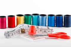 Red scissors, measuring tape and thimble with spools of thread on white background. Royalty Free Stock Photo