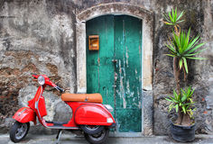 Red scooter. Photo of red scooter near green door and palm Royalty Free Stock Photography