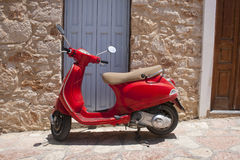 Red scooter. In front of stone wall and blue door Royalty Free Stock Image
