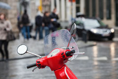 Red scooter in front of a traffic scene Royalty Free Stock Photography