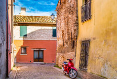 Red scooter in narrow street Stock Photo