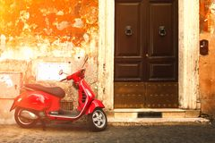 Red scooter on an old narrow street in Rome royalty free stock photos