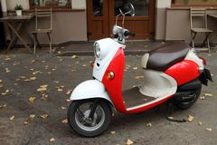 Red scooter parked at the entrance to the cafe stock photos