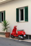 Red scooter parked beside house Stock Photo