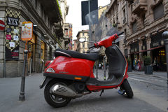 Red scooter parked in one of the Milan central streets Stock Photo