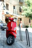 Red scooter parked in the street in the european sity royalty free stock image