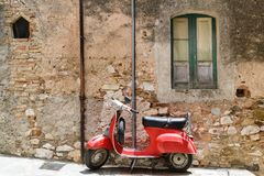 Red scooter by a rustic house. In Italy royalty free stock images