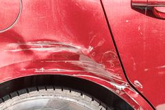 Red scratched car with damaged paint in crash accident on the street or collision on parking lot in the city.  royalty free stock photos