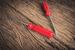 Red screwdriver on wooden background Royalty Free Stock Photo