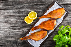 Red Sea Bass on wooden plank, top view. Red Sea Bass on a parchment paper on an old wooden table with basil leaves, lemon slices on the background, top view Royalty Free Stock Photo