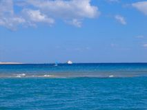 Red sea in Egypt reef, sailboat with blue sails and white yacht royalty free stock images