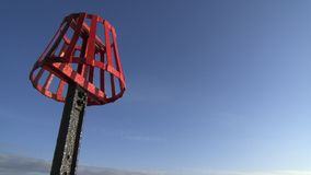 Red sea mark. On a black metal pole against a blue sky Stock Image