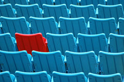 Red Seat. A red seat among rows of blue seats Royalty Free Stock Photos