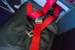 Red seat belt on the seat in the airplane. Red seat belt on the empty seat in the airplane stock photography