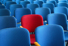 Red seat standing out. Red seat as an eyecatcher in the middle of rows of empty blue seats, conceptual image Stock Photos