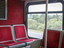 Red seats in back of commuter bus moving on high way stock image