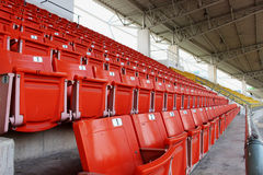 Red seats on the grandstand in the stadium Stock Images