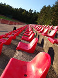 Red seats. In stadium located in forest stock images