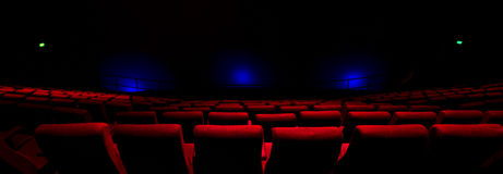 Red Seats in a Theatre. Rows of red seats in a dark theatre with blue lights shining on the screen stock photo
