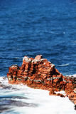 Red sedimentary sea cliff, miniature style Royalty Free Stock Photo