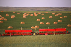 Red seeders and hay bales Stock Photo