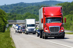 A red semi leads a line of traffic down an interstate highway in Tennessee. Heat rising from the pavement gives background trucks and forest a cool shimmering Stock Photos