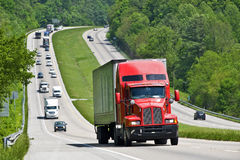 Red Semi Truck Climbing Hill On Interstate Highway. A red semi truck climbs a hill on an interstate highway Stock Photography