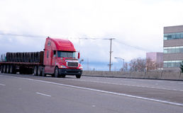 Red semi truck with flat bed trailer transporting industrial car Royalty Free Stock Photography