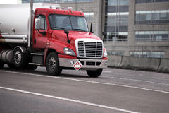 Red semi truck moving on highway and transporting fuel in tank Royalty Free Stock Photo